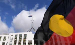 Australian Parliament House is seen through an Aboriginal flag in Canberra