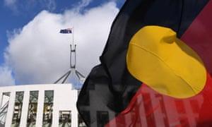 Parliament House is seen through an Aboriginal flag