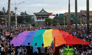 Marchers hold a rainbow flag in Taipei