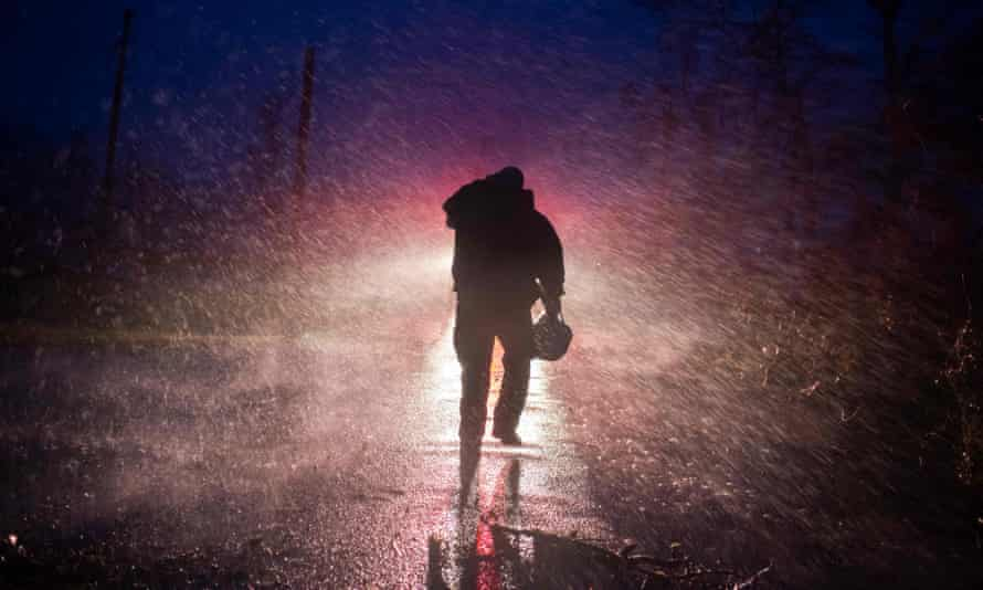 Montegut fire chief Toby Henry walks back to his fire truck in the rain in Bourg, Louisiana.