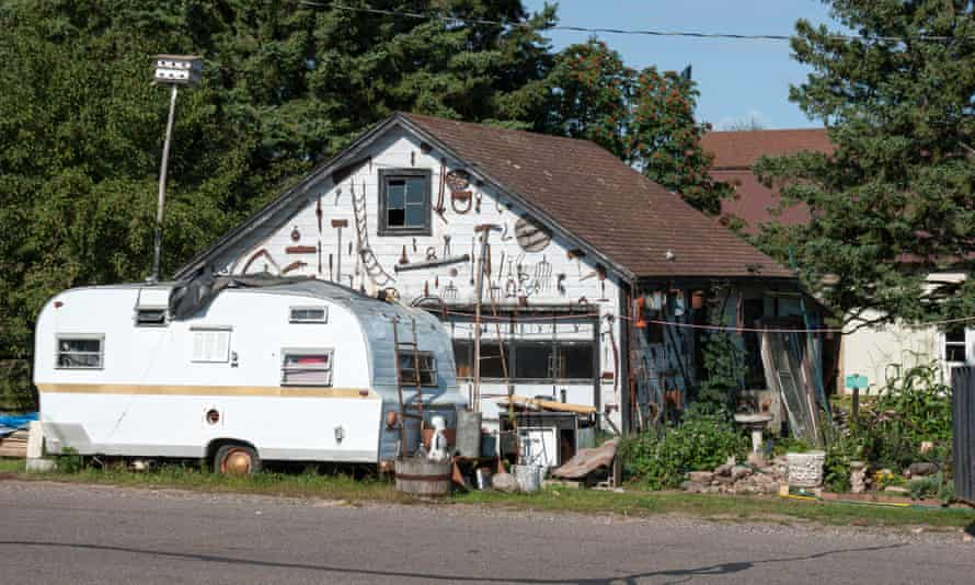 A camper trailer parked in front of a garage covered with antique farm and forestry implements
