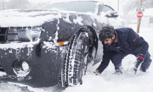 Srikanth Bellamkonda of Andhra Pradesh, India, digs out his car after getting stuck in the snow on Friday, in Bowling Green, Kentucky.