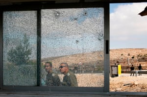 Members of the Israeli security forces walk past the shattered glass of the security post at the entrance to the West Bank settlement of Har Adar after a Palestinian opened fire on security personnel in a fatal attack before being shot dead.