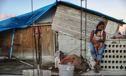 A mother holds her nine-month-old baby at their makeshift home, under reconstruction after being mostly destroyed by Hurricane Maria, in San Isidro, Puerto Rico, on 23 December 2017.