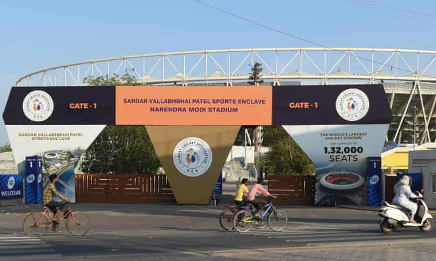 Cyclists cycle past the main entrance of IPL venue Narendra Modi Stadium in Ahmedabad, India