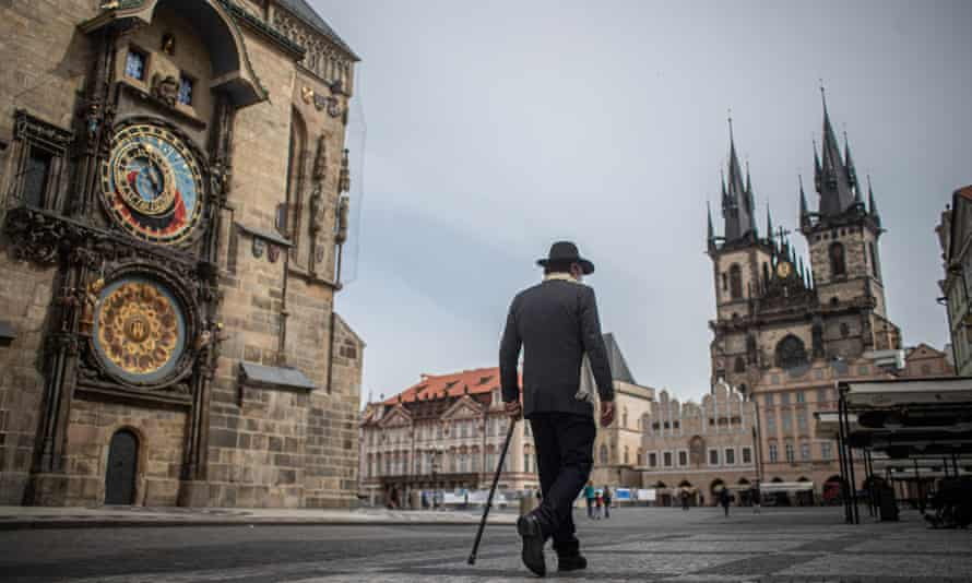 Man walking across near-deserted Old Town Square in Prague.