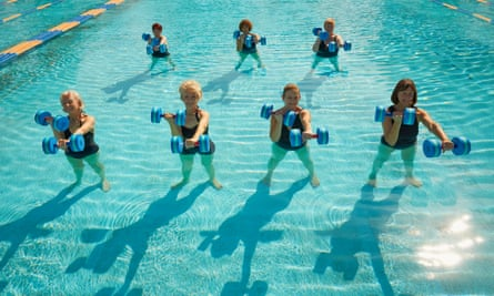 Women taking a fitness class in swimming pool.