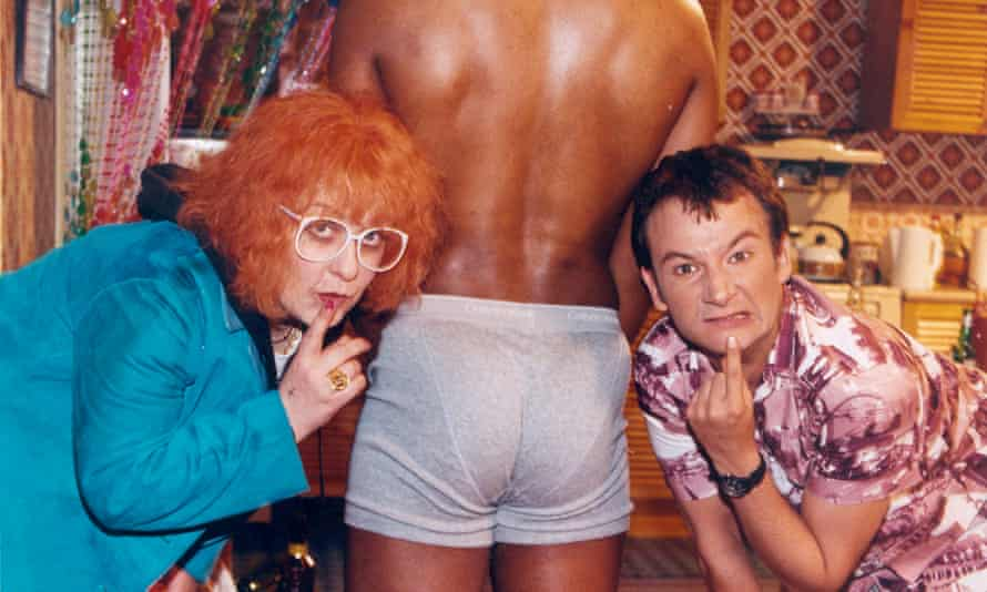 Scene from the television programme Gimme Gimme Gimme showing Linda La Hughes (KATHY BURKE) and Tom Farrell (James Dreyfus) standing either side of a muscular man in boxer shorts