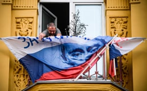 A man fixes a Vladimir Putin presidential campaign flag a balcony in Moscow, Russia