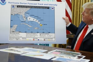 Donald Trump holds a chart in which the projected path of Hurricane Dorian appears to have been extended in makeshift fashion to include Alabama by means of a Sharpie pen.