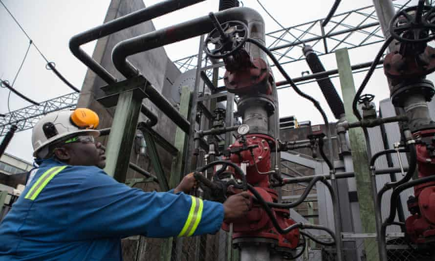 An employee adjusts a pipe at a power plant in Port Harcourt, Nigeria