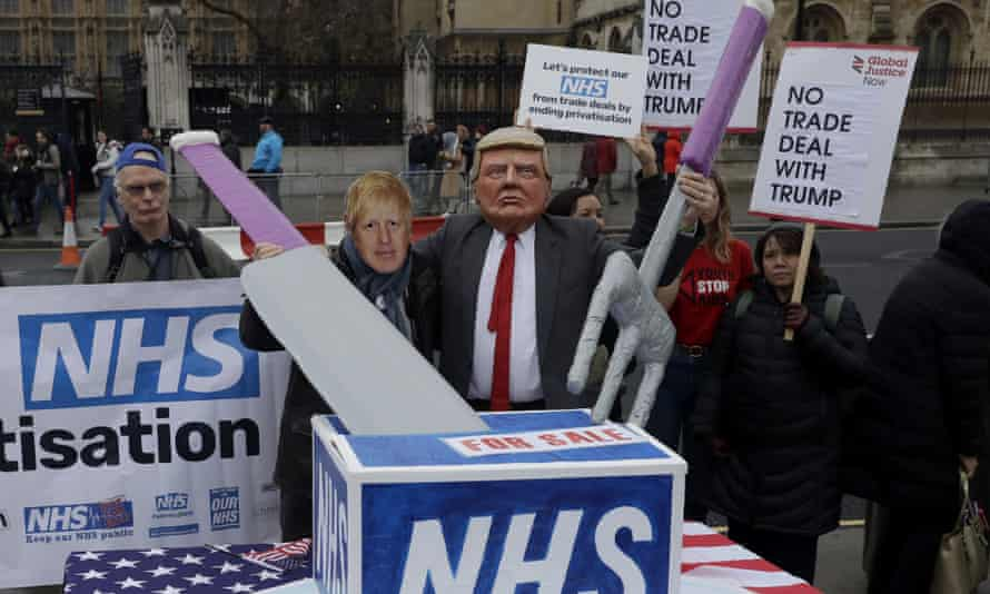 NHS campaigners with masks of Boris Johnson and Donald Trump take part in a demonstration on Parliament Square