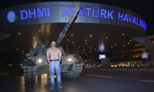 A man stands in front of a tank, part of the coup forces, at the entrance to Istanbul's Ataturk airport