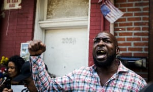 A demonstrator yells in protest at the location where Eric Garner was killed one year earlier in New York.