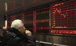 An investor monitors stock prices at a brokerage in Beijing on Tuesday, December 31.