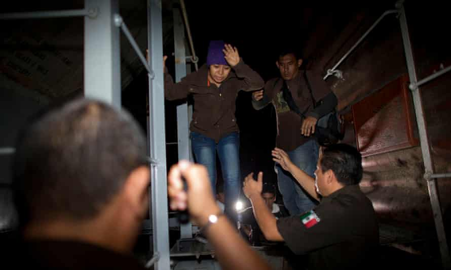 Immigration officials remove Central American migrants from a northbound freight train during an after-midnight raid by federal police in San Ramon, Mexico, last year.