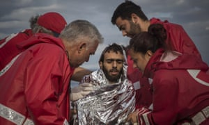 Members of the Greek Red Cross help a refugee who has just landed on a shore at Lesbos.