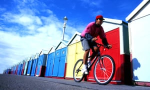 A teenager cycles past beach huts on Brighton's seafront.