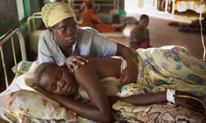A mother cares for her daughter suffering from malaria in a hospital in Amuria, Uganda
