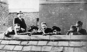 Irish rebels lying in wait on a roof getting ready to fire during the Easter Rising, Ireland, 1916