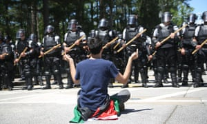 A protester gives two middle fingers to police officers in riot gear.