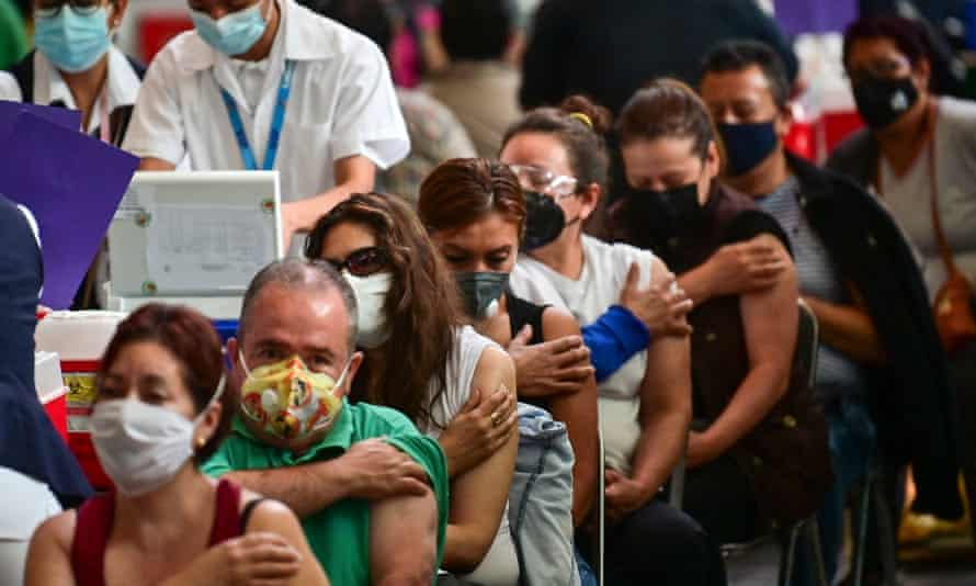 People wait after receiving doses of the Covid vaccine on 11 May in Mexico City.