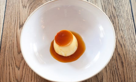 A yellow crème caramel with an orange brown top and sauce in the centre of a large round bowled plate