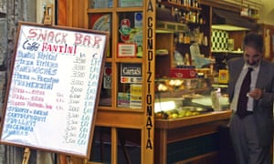 A man checks his bill in a bar in downtown Rome where prices are expressed in euros and Italian lire, 16 October 2001