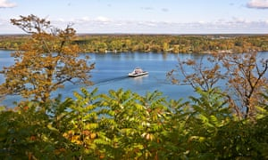 The Glenora Ferry is a free service that shuttles cars and passengers to Prince Edward County, Ontario, Canada. The ferry is shown in mid-crossing amid a green countryside landscape.