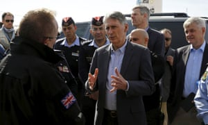 Philip Hammond speaks with former British police officers at a refugee camp in Jordan.