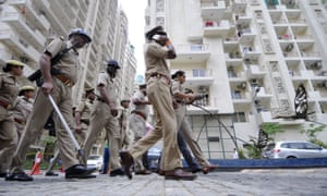 Police in a New Delhi suburb stand guard after locals attacked the housing colony in July, alleging mistreatment of a housemaid.