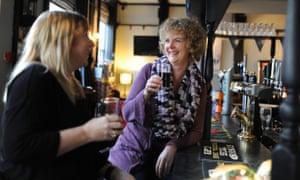 two women drink in a pub