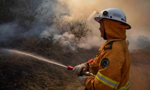 A firefighter tackles a blaze at Canungra in Queensland