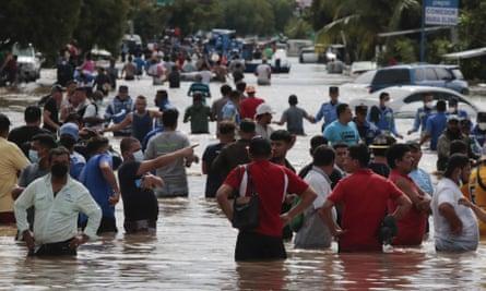 Residents wade through a flooded road in the aftermath of Hurricane Eta in Planeta, Honduras.