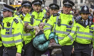 Police arrest protesters as they block traffic on London's Oxford Circus. The demonstrators' tactic of lying down meant four officers were needed to make an arrest.