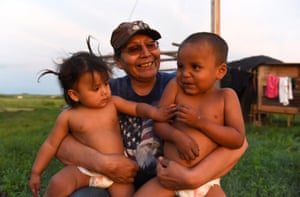 """Beatrice Lookinghorse sits with two of her grandchildren, Linda Lookinghorse and Cody James Lookinghorse, in the backyard of her home on the Cheyenne River Reservation in Green Grass, South Dakota. Beatrice Lookinghorse is related to several of the Fort Laramie treaty riders who live with her. Beatrice also raises other children from the extended Lookinghorse family. """"I promised my father that none of his grandkids would ever be put in the (foster care) system,"""" she said."""