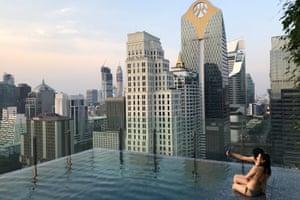 Tourists enjoy a swimming pool at a hotel in Bangkok, Thailand
