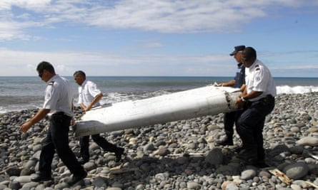 Officers carrying pieces of debris from an unidentified aircraft apparently washed ashore in Saint-Andre de la Reunion, eastern La Reunion island, France, 29 July 2015.