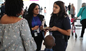 A Border Force official speaks to passengers following their arrival at Heathrow airport