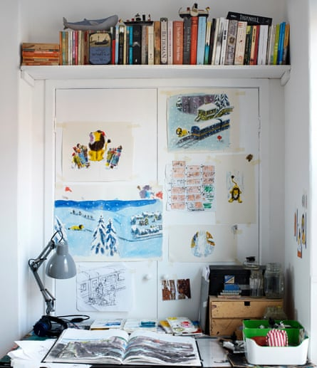 An open book on a desk, with illustrations taped to the wall