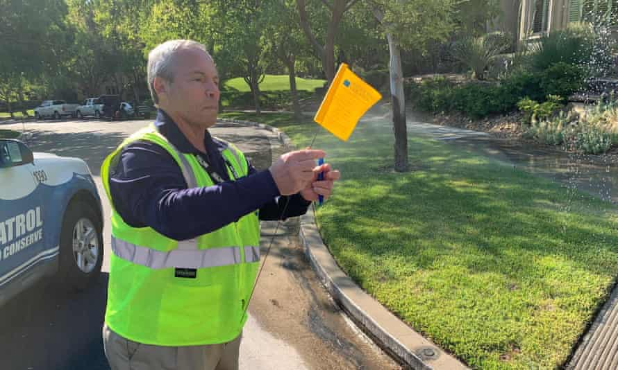 Perry Kaye, a water waste investigator in Las Vegas, Nevada, issues a yellow warning flag because of a faulty sprinkler.