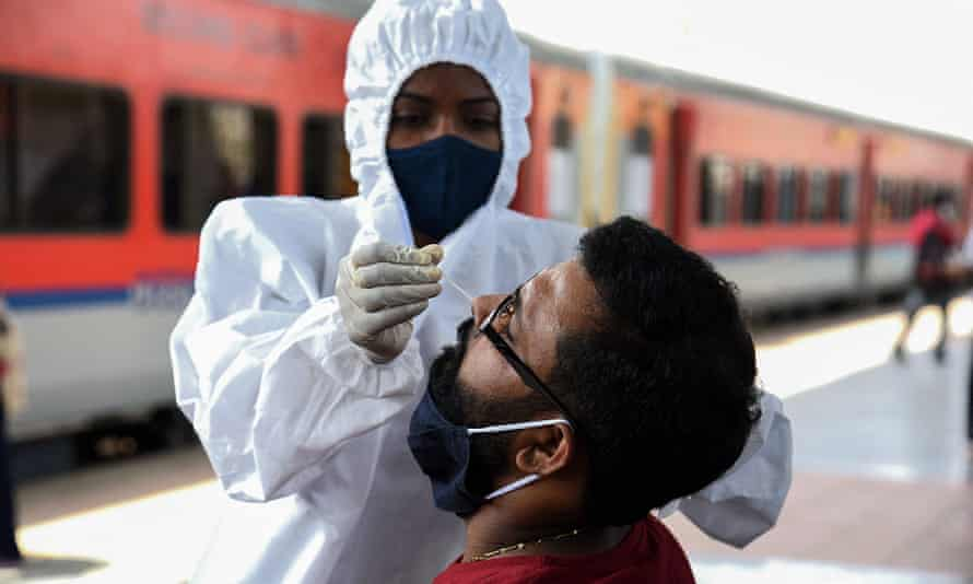 A train passenger is tested for Covid after arriving in Mumbai.