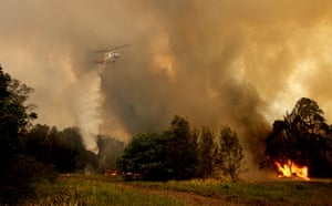 A fire-bombing helicopter works to contain a bushfire along Old Bar Road in Old Bar, NSW, on Saturday