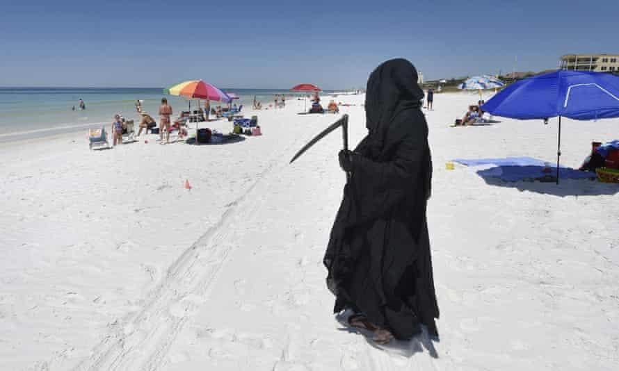 Florida attorney Daniel Uhlfelder, dressed as the Grim Reaper, walks the newly-opened beach near Destin, Florida, on 1 May 2020.