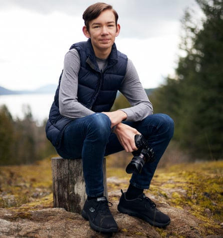 Young climate activist Dylan D'Haeze, 16, photographed in Washington state, US, sitting on a rock, holding a camera
