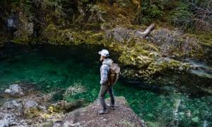 Man standing on rock looking away at river, Opal Creek,