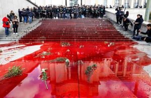 Members of the action group Extinction Rebellion gather after spilling fake blood on the steps of the Trocadero esplanade in Paris during a demonstration about the decline of biodiversity