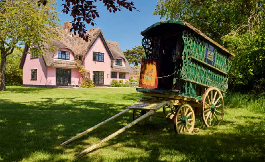 The pink exterior of the home of fashion designers Justin Thornton and Thea Bregazzi in Walberswick, Suffolk, with a green vintage caravan in front