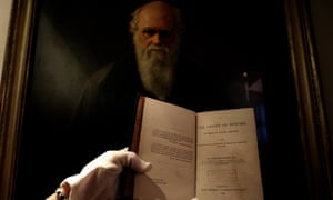 A first edition of Charles Darwin's landmark book, in front of a portrait of Darwin at a 2010 exhibition celebrating The Royal Society.
