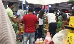 People buying food staples at a supermarket in Doha, Qatar.